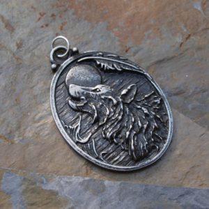 medailon, vlk vyje na úpňkový měsíc,indiánské péro,divočina
